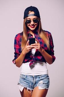 Portret szczęśliwa młoda dziewczyna za pomocą smartfona na białym tle na szarej ścianie