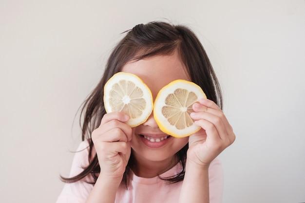 Portret szczęśliwa młoda dziewczynka zasłaniając oczy plasterkami cytryny, zdrowy styl życia, wegańskie, dieta roślinna, dzieciak bawiący się jedzeniem