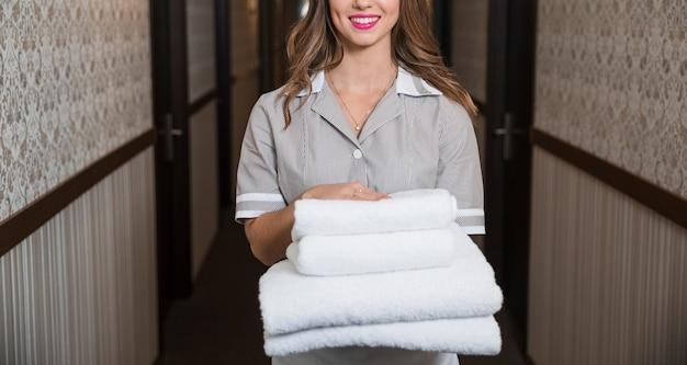 Portret szczęśliwa młoda gosposia pozycja w korytarza mieniu składał miękkich ręczniki