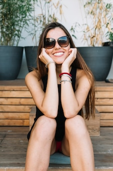 Portret szczęśliwa młoda kobieta jest ubranym okulary przeciwsłonecznych