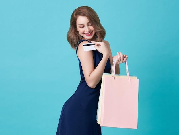 Portret szczęśliwa młoda kobieta pokazuje kredytową kartę i torba na zakupy