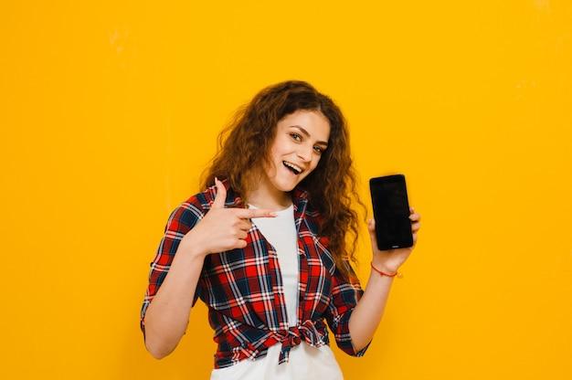 Portret szczęśliwa młoda kobieta pokazuje pustego ekranu telefon komórkowego odizolowywającego nad kolor żółty ścianą