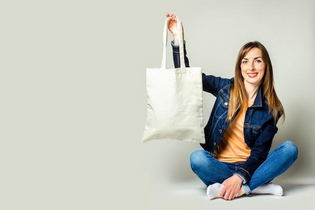 Portret szczęśliwa młoda kobieta siedzi ze skrzyżowanymi nogami, trzymając lnianą torbę z zakupami na jasnym tle