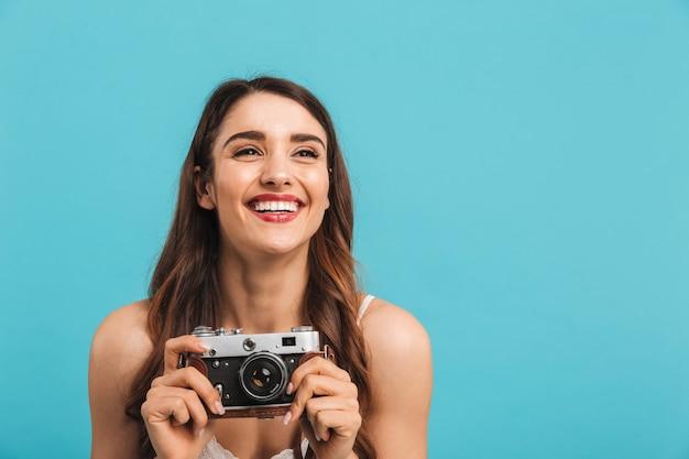 Portret szczęśliwa młoda kobieta trzyma aparat fotograficzny
