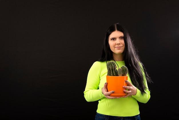 Portret szczęśliwa młoda kobieta trzyma kaktus doniczkową roślinę na białym tle