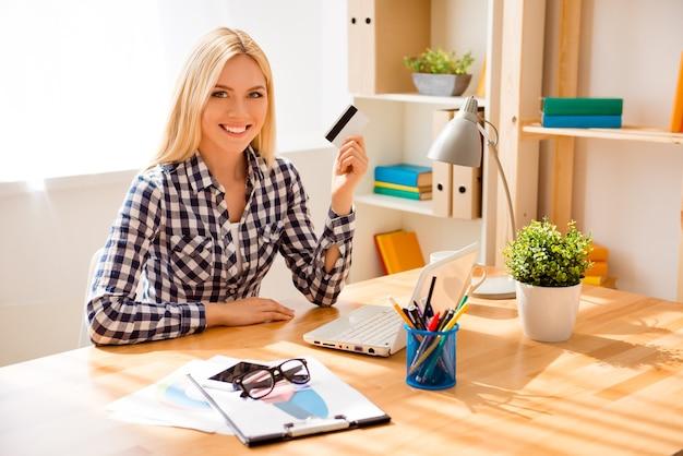 Portret szczęśliwa młoda kobieta trzyma kartę bankową i robi zakupy w internecie