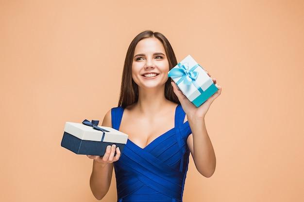 Portret szczęśliwa młoda kobieta trzyma prezenty na białym tle na brązowym tle z szczęśliwymi emocjami