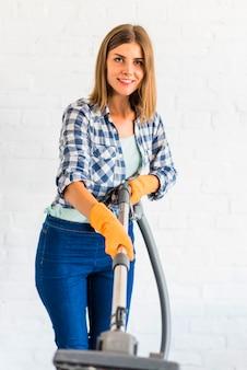 Portret szczęśliwa młoda kobieta trzyma próżniowego cleaner