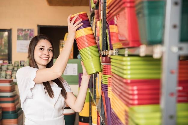 Portret szczęśliwa młoda kobieta układa kolorowe doniczkowe rośliny w półce