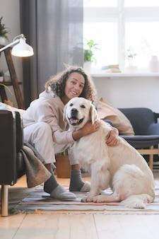 Portret szczęśliwa młoda kobieta uśmiecha się do kamery, siedząc na podłodze w pokoju i obejmując psa