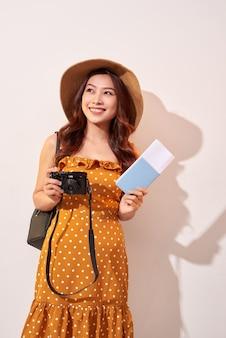 Portret szczęśliwa młoda kobieta w kapeluszu, trzymając aparat i pokazując paszport, stojąc na białym tle nad beżową ścianą