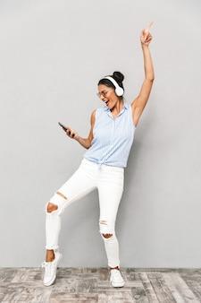 Portret szczęśliwa młoda kobieta w okularach przeciwsłonecznych na białym tle, trzymając telefon komórkowy, słuchanie muzyki w słuchawkach, taniec