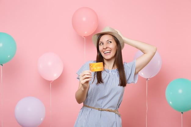 Portret szczęśliwa młoda kobieta w słomkowym letnim kapeluszu niebieska sukienka trzymaj kartę kredytową trzymając się głowy patrząc na różowym tle z kolorowymi balonami. urodziny wakacje party ludzie szczere emocje.