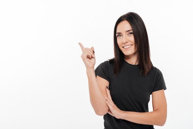 Portret szczęśliwa młoda kobieta wskazuje palec daleko od