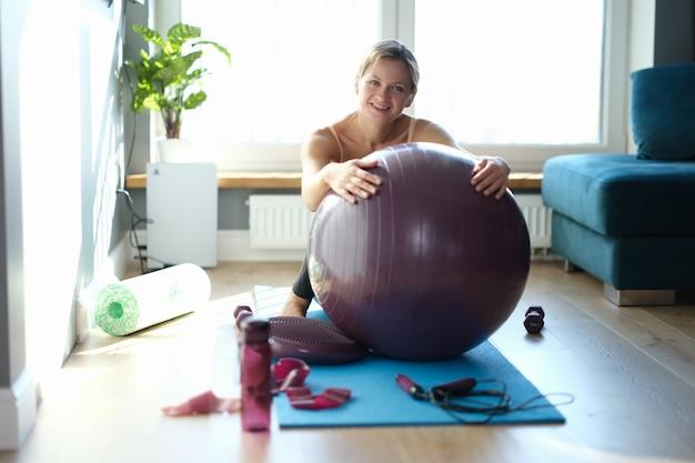 Portret szczęśliwa młoda kobieta z dużą piłką gimnastyczną na dywanie w domu. ćwiczenia fitball w koncepcji domu