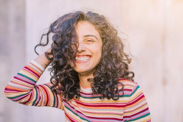 Portret szczęśliwa młoda kobieta z kędzierzawym włosy