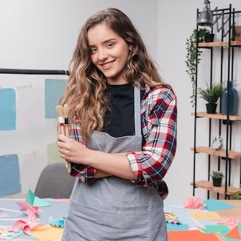 Portret szczęśliwa młoda kobieta z mienia paintbrush