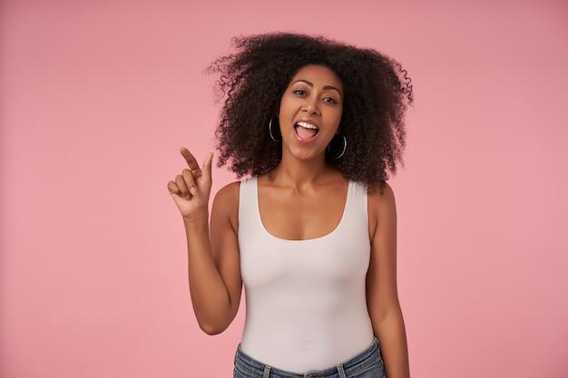 Portret szczęśliwa młoda kręcona dama z przypadkową fryzurą radośnie podnoszącą rękę, ubrana w białą koszulę i dżinsy ubranie na różowo