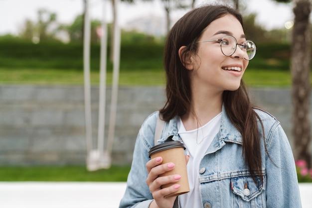 Portret szczęśliwa młoda ładna kobieta studentka spaceru na świeżym powietrzu w zielonym parku przyrody picia kawy.