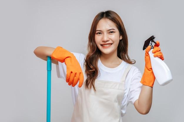 Portret szczęśliwa młoda ładna kobieta w fartuchu i gumowych rękawiczkach, trzymając butelkę z rozpylaczem, przygotowując się do czyszczenia, uśmiechu i patrząc na kamerę, kopia przestrzeń