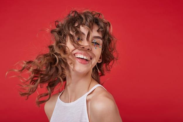Portret szczęśliwa młoda ładna kobieta z kręconymi włosami i świątecznym makeubp śmiejąc się wesoło i patrząc, pozowanie w białej koszuli