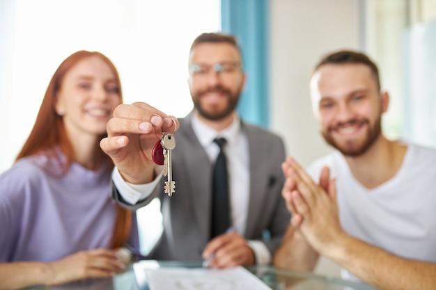 Portret szczęśliwa młoda nowo małżeńska rodzina z agentem nieruchomości