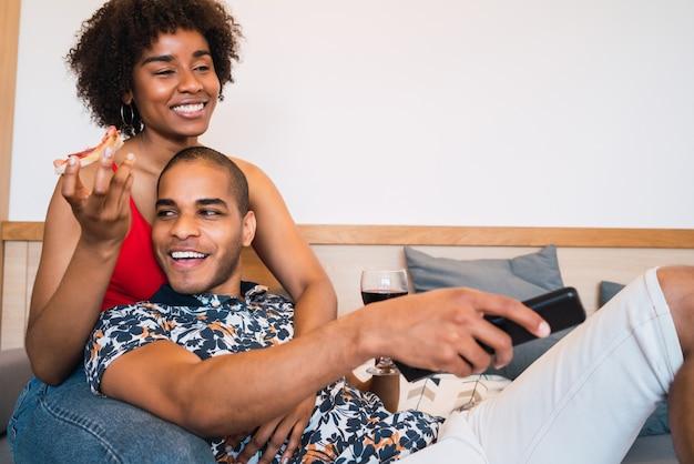 Portret szczęśliwa młoda para łacińskiej spędzać czas razem i oglądać telewizję w ich domu. koncepcja stylu życia i relacji.