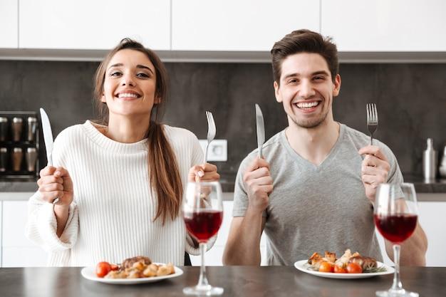 Portret szczęśliwa młoda para siedzi przy stole w kuchni