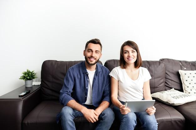 Portret szczęśliwa młoda para w nieformalnych strojach siedzi na wygodnej kanapie w domu i ogląda film za pomocą cyfrowego tabletu