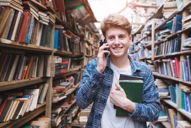 Portret szczęśliwa młody człowiek pozycja z książkami w jego rękach w bibliotece publicznej
