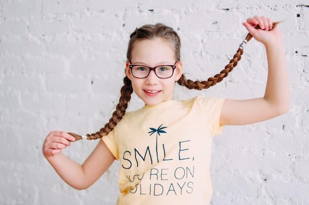 Portret szczęśliwa nastolatka dziewczyna w żółtej koszulce z śmiesznymi pigtails na białym ściana z cegieł tle