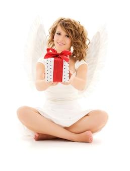 Portret szczęśliwa nastoletnia dziewczyna anioła z prezentem na białej ścianie