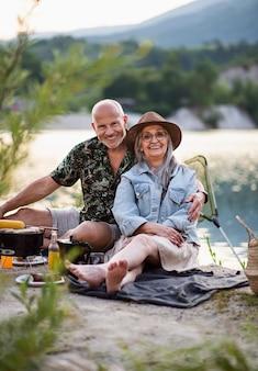 Portret szczęśliwa para starszych odpoczynku na letnie wakacje, grill nad jeziorem.