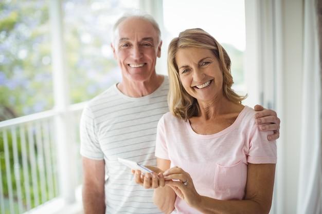 Portret szczęśliwa para starszych stojących na balkonie z telefonem komórkowym