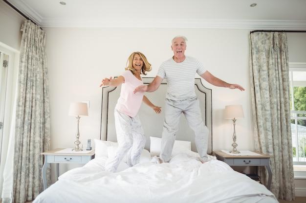 Portret szczęśliwa para starszych tańczy na łóżku