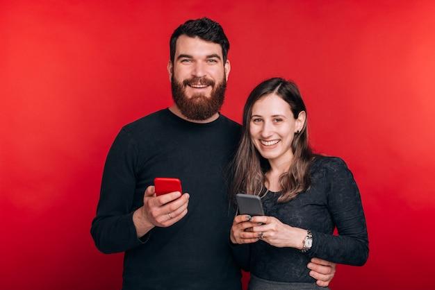 Portret szczęśliwa para trzyma smartfony i patrzeje kamerę