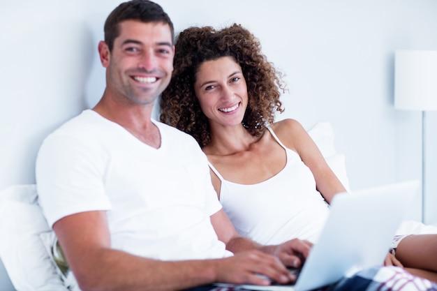 Portret szczęśliwa para używa laptop na łóżku