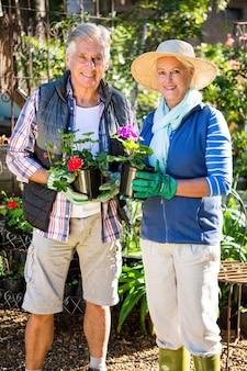 Portret szczęśliwa para z doniczkowymi roślinami przy ogródem