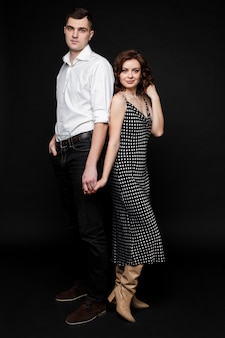 Portret szczęśliwa para zakochanych stoi i ściska razem, obraz na białym tle na czarnej ścianie