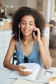 Portret szczęśliwa piękna afrykańska kobieta słucha muzyka w hełmofonach uśmiecha się siedzieć w kawiarni. zamknięte oczy.