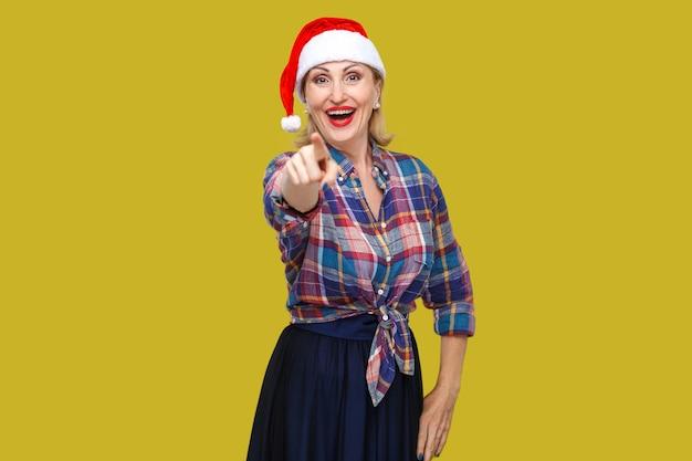 Portret szczęśliwa piękna dorosła kobieta w czerwonej czapce santa i kraciastej koszuli stojącej, wskazując palcem i szydząc z toothy uśmiechnięty, patrząc na kamery. wewnątrz, strzał studyjny, żółte tło