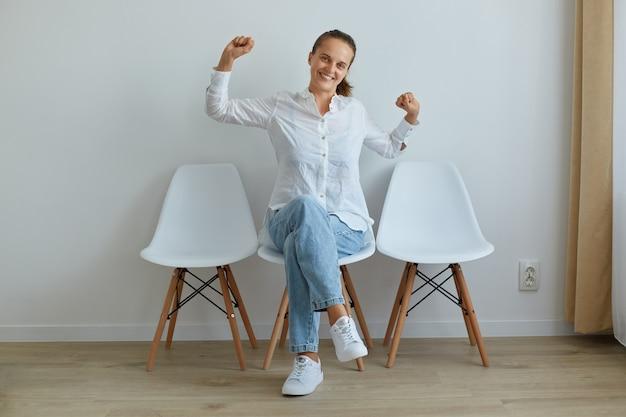 Portret szczęśliwa piękna kobieta ubrana w białą koszulę i dżinsy podniosła ramiona, wyciągając ręce, siedząc na krześle przed lekką ścianą w pomieszczeniu, patrząc uśmiechając się do kamery.
