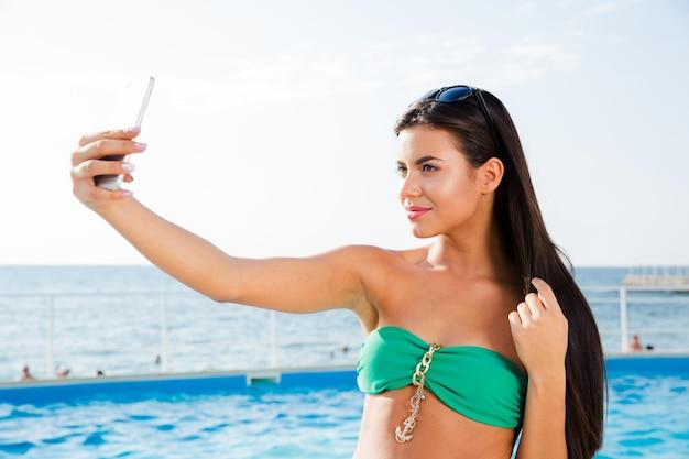 Portret szczęśliwa piękna kobieta w bikini co selfie zdjęcie na smartfonie na zewnątrz