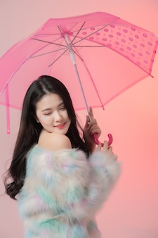 Portret szczęśliwa piękna młoda azjatycka kobieta trzyma parasol na różowo
