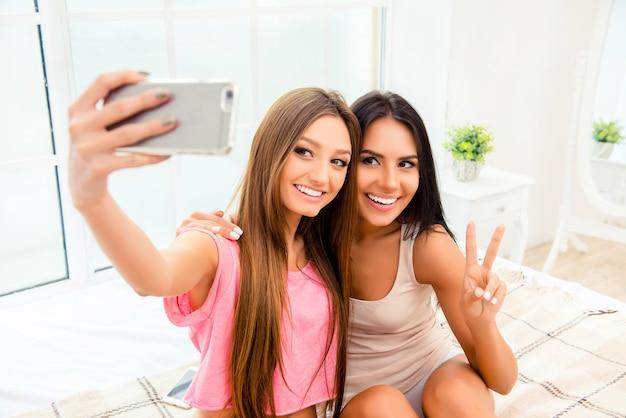 Portret szczęśliwa piękna młoda dziewczyna przy selfie