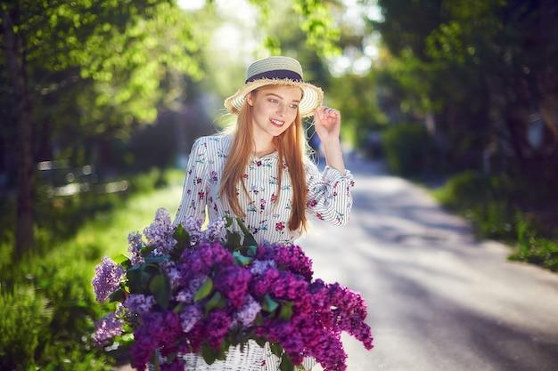 Portret szczęśliwa piękna młoda dziewczyna z rocznika rower i kwiaty na tle miasta w słońcu na zewnątrz. rower z koszem pełnym kwiatów. koncepcja aktywnego wypoczynku.