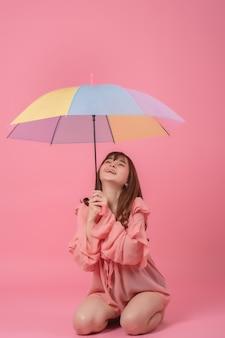 Portret szczęśliwa piękna młoda kobieta azjatyckich trzymając parasol, uśmiechając się na różowo