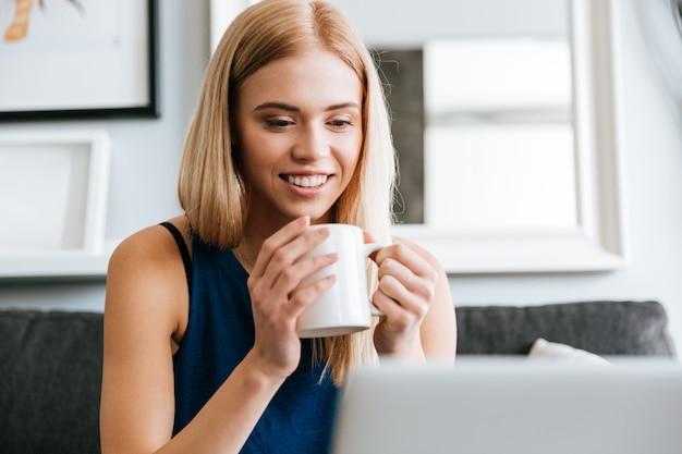 Portret szczęśliwa piękna młoda kobieta pije kawę w domu
