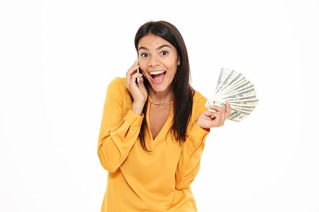 Portret szczęśliwa podekscytowana kobieta opowiada na telefonie komórkowym