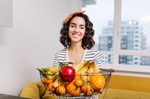 Portret szczęśliwa podekscytowana młoda kobieta uśmiecha się z owocami w nowoczesnym mieszkaniu. cytrusy, banan, jabłko, mandarynki, szczęście, radosne, prawdziwe pozytywne emocje, słodkie